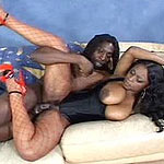 Ebony guy pounds black babe in stockings on couch